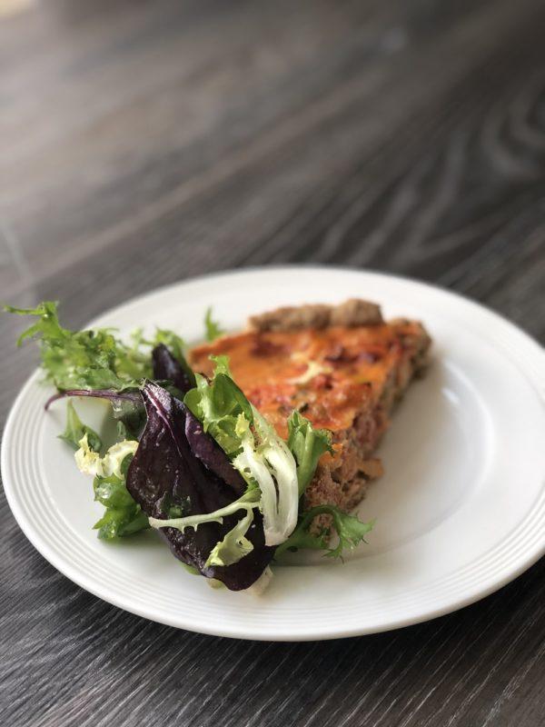 Et stykke quiche eller pai med tomat og sellerirot og salat
