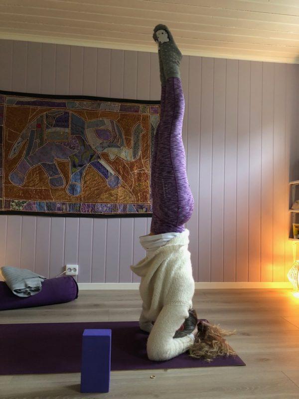 Yogaposisjon hodestående kvinne på yogamatte