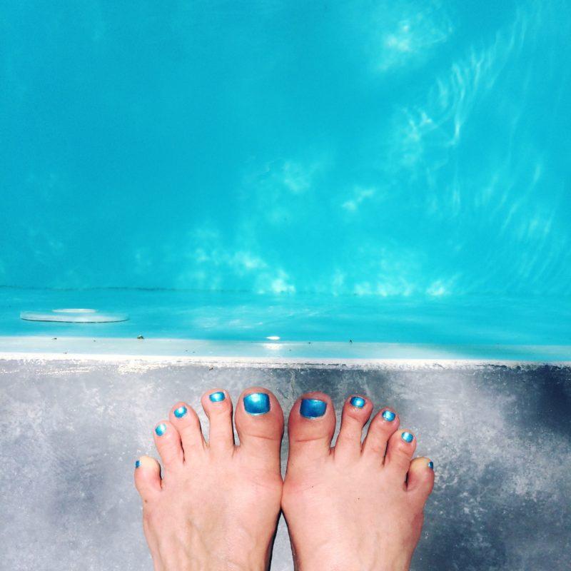Føtter med turkis neglelakk på kanten av et basseng
