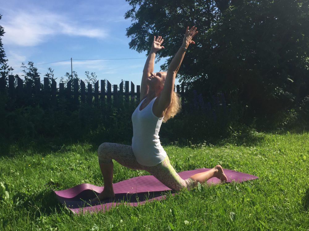 Kvinne utendørs på lilla yogamatte i crescent pose