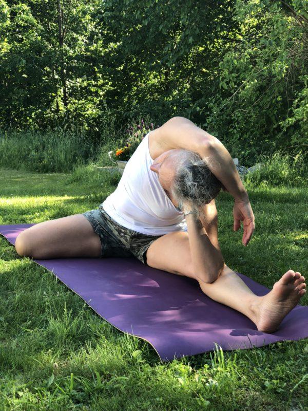 Yoga asana utendørs kvinne på lilla matte på grønt gress