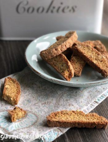 Biscotti med pistasjnøtter og sitronskall, på skål og liten duk, kakeboks i bakgrunnen