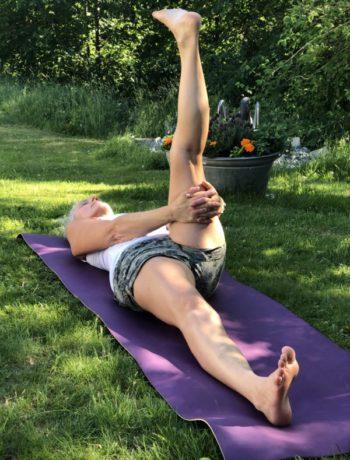 Yoga kvinne utendørs på matte på plen