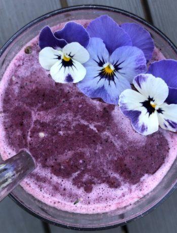 Lilla smoothie med blåbær grønnkål og spiselige blomster fioler