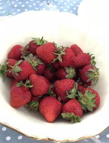 En hvit skål med røde jordbær med grønn hams på