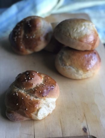 Rundstykker med oliven og fine rundstykker i haug på bordplate