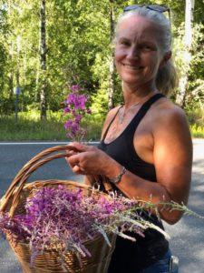 Kvinne i singlett med kurv full av geitrams blomster