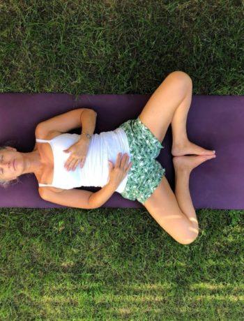 Kvinne på yogamatte på gresset i hvilende sommerfugl yogaposisjon