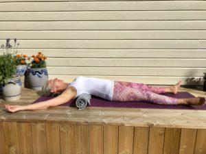 Kvinne i yogaposisjon hjerteåpner på rull utendørs