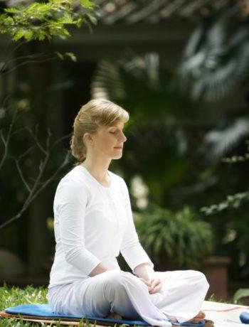 Kvinne i hvite klær mediterer utendørs