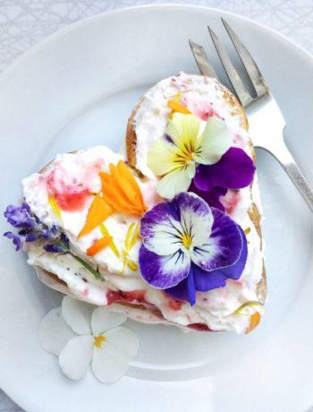 Hjerte vaffel med kremost og blomster på tallerken