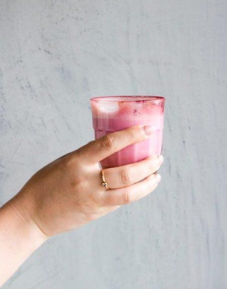 Hånd holder glass med rosa drikk