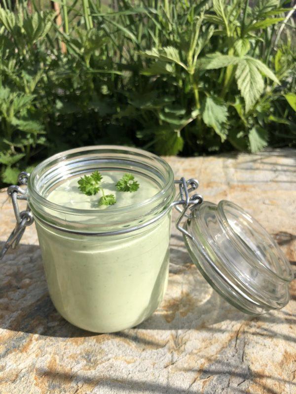 grønn dressing i glass på bord innendørs
