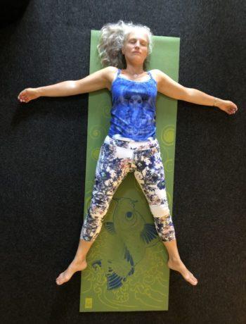 Kvinne ligger på rygg på yogamatte