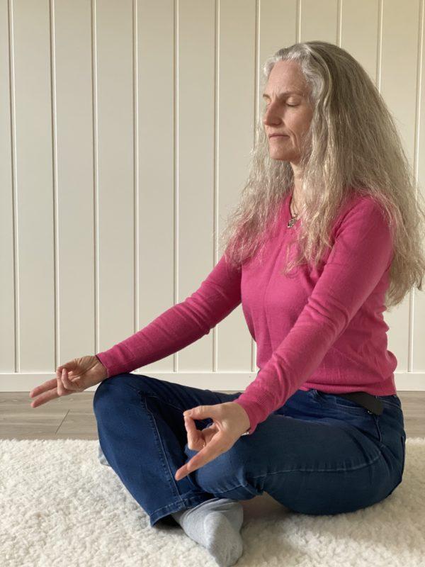 Kvinne mediterer innendørs