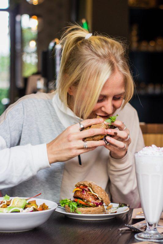 Kvinne som spiser hamburger innendørs